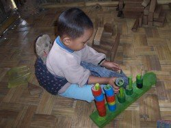 child-in-kachin-village-preschool-playing-with-community-made-toys